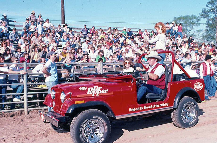 Grady Spikes drives a Dr. Pepper promotional jeep around the rodeo arena with the night's entertainer at the Montgomery County Fair in the mid-1980s. Spikes was a member of the fair association among the many activities he supported in the Conroe area. At the time, he also worked for Dr. Pepper.