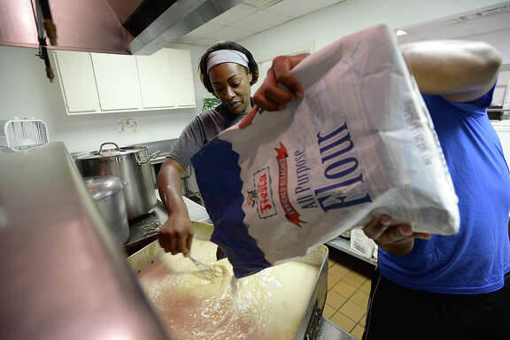 Nationally known chef and Beaumont native Tiffany Derry gets help making her roux from Michael Thomas while preparing for a dinner service at Ebenezer Missionary Baptist Church Tuesday. She and friends from Dallas arrived in Beaumont Monday with a truckload of food to cook for those in need as they recover from Tropical Storm Harvey's devastating impact on the region. Derry said additional donations of food and supplies continue to pour in, with Houston-based Midtown Kitchen Collective shipping hundreds of pounds of meat and vegetables to Beaumont as of Tuesday afternoon. Derry plans to be in the area serving meals through Thursday. She will offer two meals, lunch and dinner, Wednesday. The church is also a donation and distribution center for those in need of food, water, and other necessities. Photo taken Tuesday, September 5, 2017 Kim Brent/The Enterprise