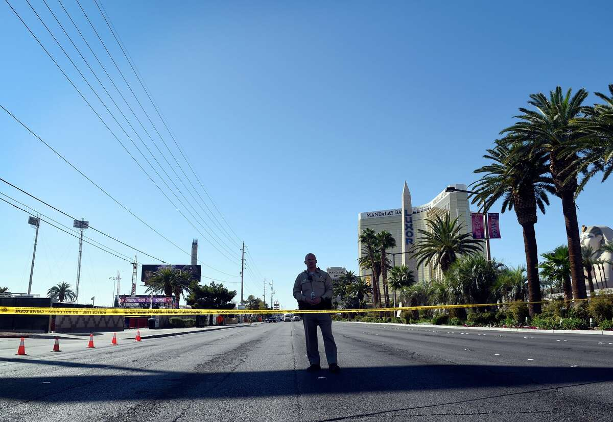 A Las Vegas police officer stands guard as traffic continues to be blocked on the Las Vegas Strip after a lone gunman opened fired on the Route 91 Harvest country music festival on October 2, 2017 in Las Vegas, Nevada. The gunman, identified as Stephen Paddock, 64, of Mesquite, Nevada, allegedly opened fire from a room on the 32nd floor of the Mandalay Bay Resort and Casino on the music festival, leaving at least 58 people dead and over 500 injured. According to reports, Paddock killed himself at the scene.