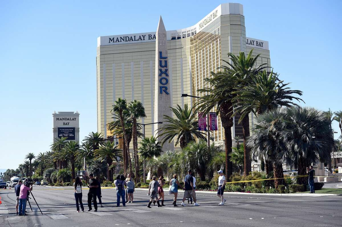 People cross the Las Vegas Strip after a lone gunman opened fired on the Route 91 Harvest country music festival on October 2, 2017 in Las Vegas, Nevada. The gunman, identified as Stephen Paddock, 64, of Mesquite, Nevada, allegedly opened fire from a room on the 32nd floor of the Mandalay Bay Resort and Casino on the music festival, leaving at least 58 people dead and over 500 injured. According to reports, Paddock killed himself at the scene.