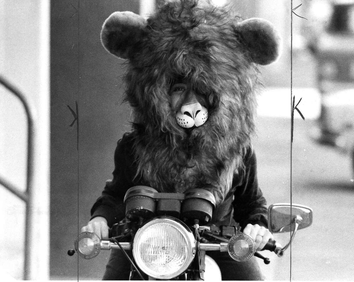 Adults in costume for various Halloween events .. A person in a lion costume rides a motorcycle Photo ran 10/27/1980, p. 16