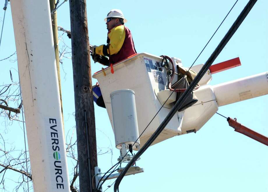 """An Eversource crew at work in Westport, Conn., in April 2016. Some 17,600 Eversource electricity customers were enrolled in """"arrearage"""" forgiveness plans last year allowing them to continue receiving service while working out payment plans for amounts past due. Photo: Cathy Zuraw / Hearst Connecticut Media / Connecticut Post"""