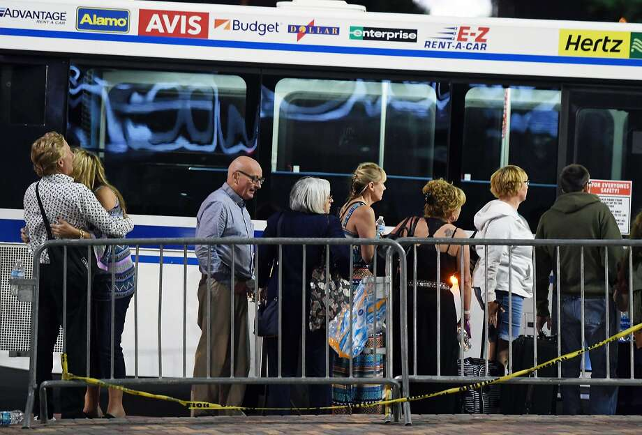 People wait to get on a McCarran International Airport rental car bus  after a mass shooting at a country music festival on October 2 in Las Vegas. The airport was briefly locked down early Sunday following Saturday night's mass shooting, which erupted at a concert site near the runways. Photo: Ethan Miller, Getty Images