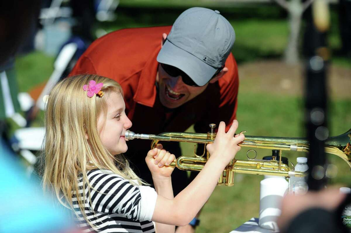 Francois Magnant, of Stamford, watches his six-year-old daughter Elodie Magnant play the trumpet for the first time during US Day 2017, a collaboration between the Stamford Public Education Foundation and MarcUS for Change, at Mill River Park in downtown Stamford, Conn. on Sunday, Oct. 1, 2017. MarcUS for Change 5K celebrates the memory of Marcus Dixon McInerney, a Stamford High School graduate who overcame many life challenges and attended West Point Academy before his life ended tragically in 2012.