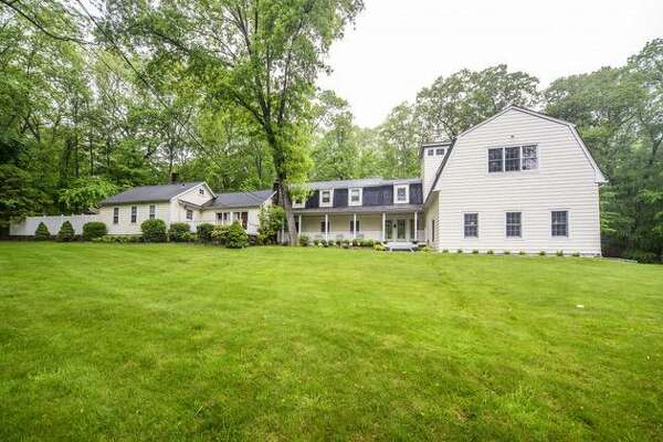The yellow Cape Cod colonial house at 1256 Catamount Road is on a two-acre property in a very rural part of Fairfield, and it adjoins Brett Woods Open Space.