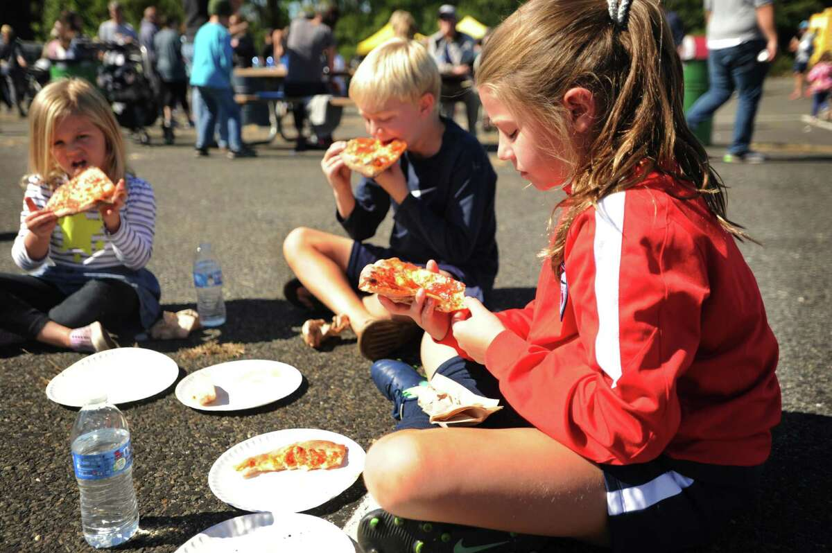 From left, Siblings Finley, 4; Kieran, 7, and Meghan Coyne, 9, of Fairfield, find a spot in the Jennings Beach parking lot to enjoy slices of pizza at the first annual Fairfield Food Truck Festival on Sunday. The event was organized by Friends of the Fairfield Public Library.