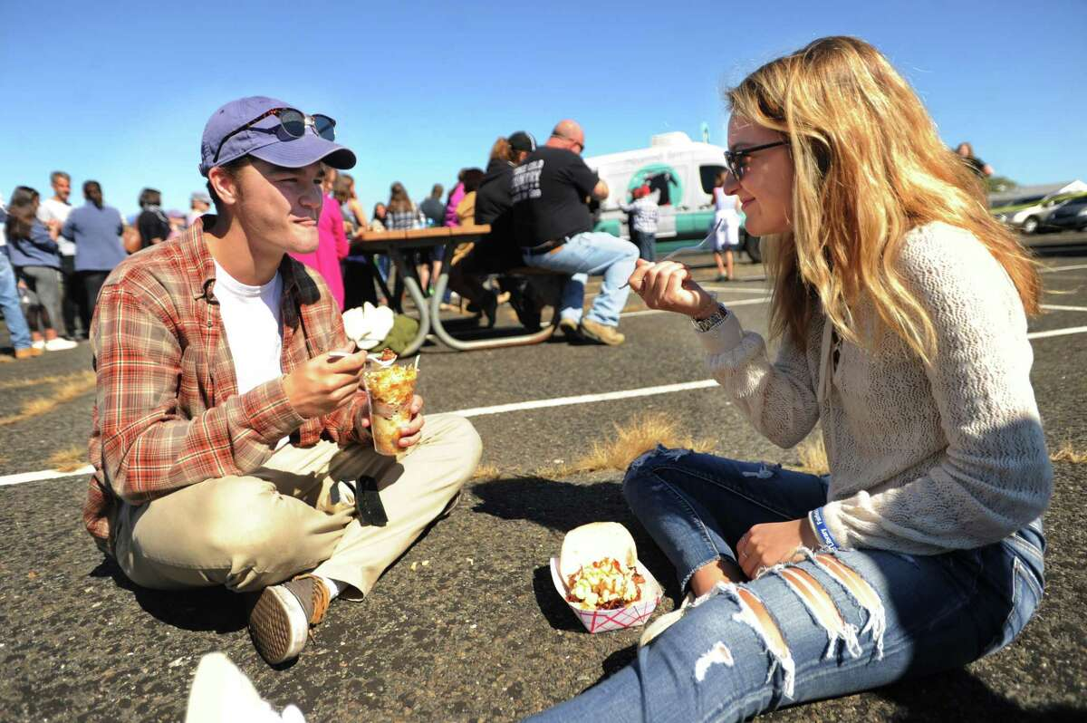 Johnny Blatt and Isabel Nikac, both of Fairfield, find a spot in the Jennings Beach parking lot to enjoy their lunch at the first annual Fairfield Food Truck Festival at Jennings Beach in Fairfield, Conn. on Sunday, October 1, 2017. The event was organized by Friends of the Fairfield Public Library.