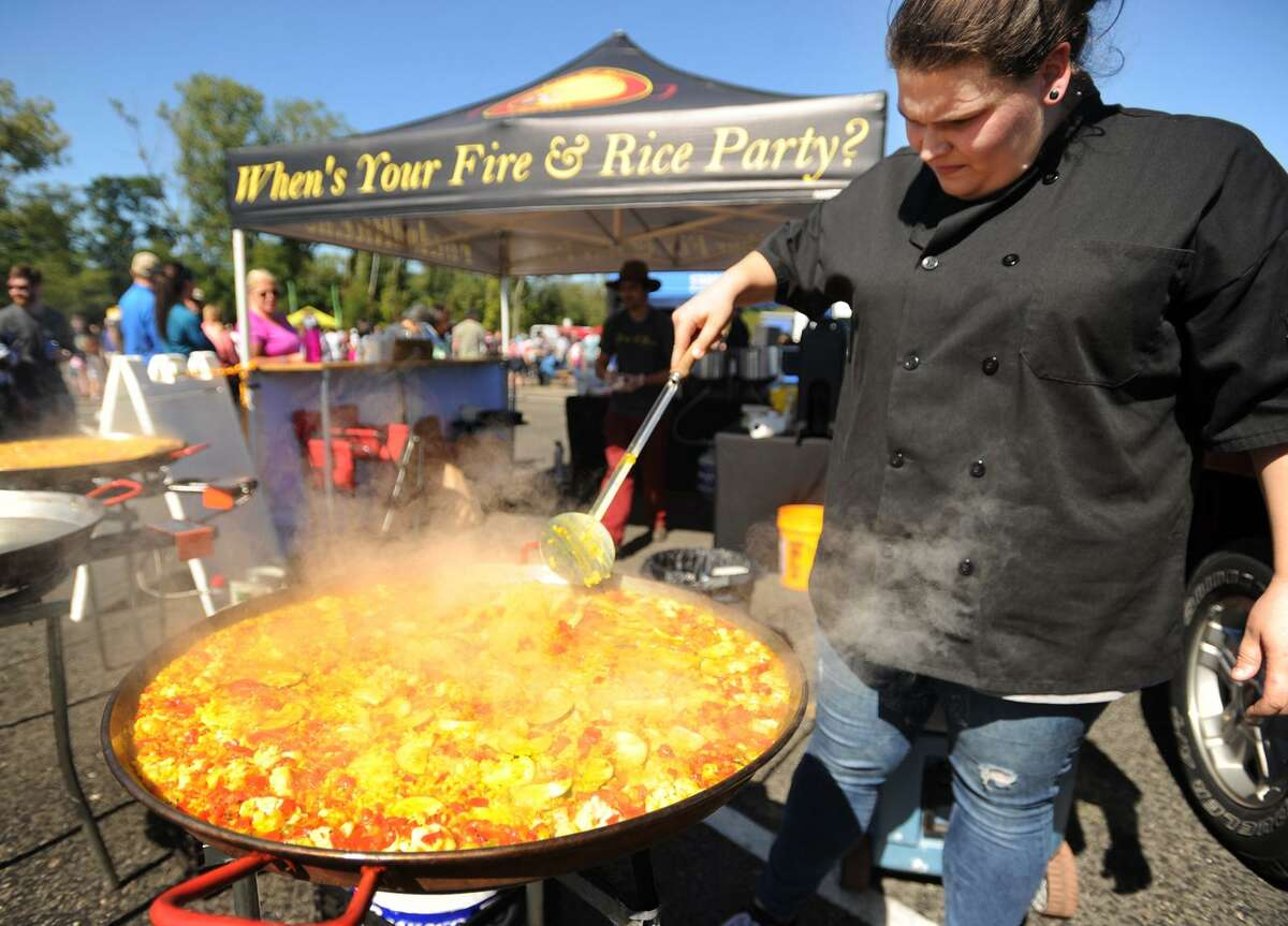 Taylor Kote, of Newtown, prepares paella for Fire & Rice Paella.