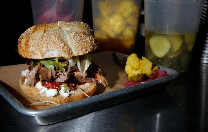 A ginger lime basted rotisserie lamb leg, on a sesame roll, with roasted nardello peppers, backyard balsamic figs, french feta, crispy papadam chips, heirloom tomatoes and house mayo, prepared by Jeff Mason the chef-owner of Pal's Takeaway, a small pop-up sandwich shop located inside Forage Kitchen, in Oakland, Ca., as seen on Thurs. September 7, 2017.