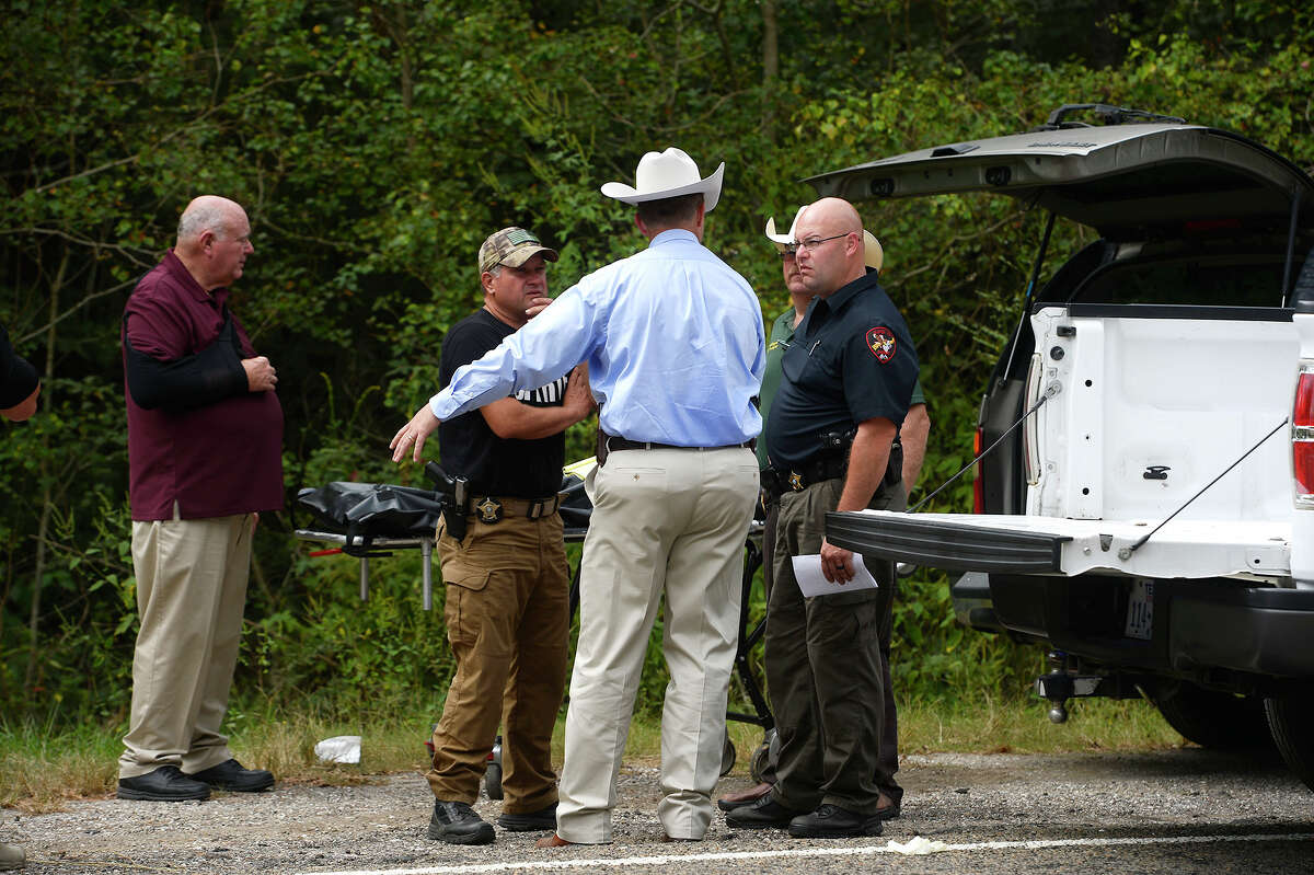 Investigators talk near the scene where a 19-year-old man's body was found along Texas 1135 in Orange County on Monday. The man is believed to be