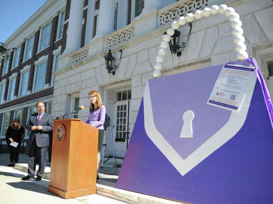 YWCA of Greenwich President and CEO Mary Lee Kiernan speaks during a ceremony marking domestic abuse awareness month in front of a large purple purse, the symbol of domestic abuse, outside Town Hall on Monday. Representatives from the YWCA and Greenwich Police department spoke about the prevalence of domestic abuse and the services the town offers. Photo: Tyler Sizemore / Hearst Connecticut Media / Greenwich Time