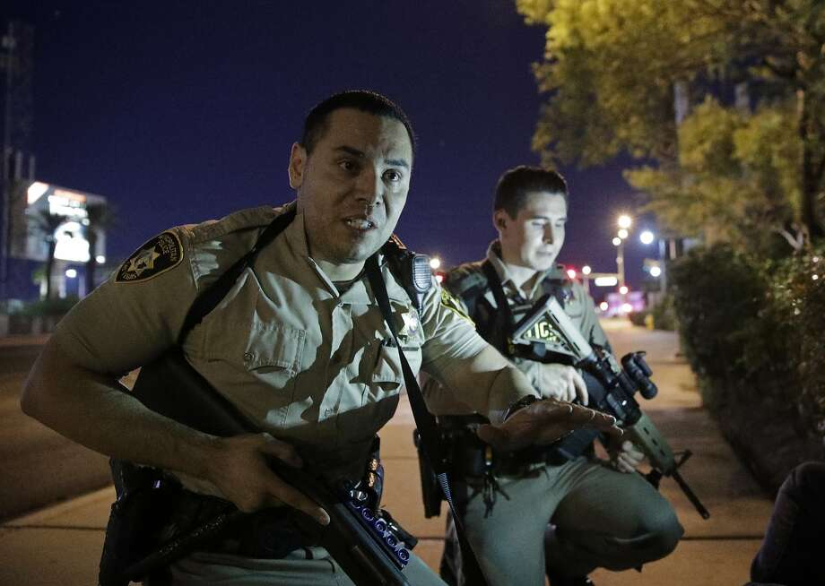 Police officers urge people to take cover near the location of the mass shooting that killed and injured people in Las Vegas. Photo: John Locher, Associated Press