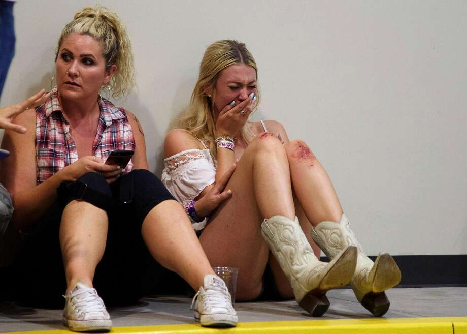 A woman cries while hiding inside the Sands Corporation plane hangar after a mass shooting in which dozens were killed at the Route 91 Harvest Festival on Sunday, Oct. 1, 2017, in Las Vegas. (Al Powers/Invision/AP) Photo: Powers Imagery, Associated Press