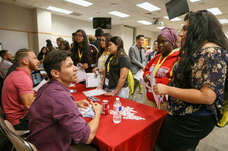 Roosevelt seniors Marissa Canales (from right), 18, and Wardo Ali, 18, visit the Rackspace table manned by Dustin Wray (left) and James Arellano during the 2017 Youth CareerCON Expo at Education Service Center . Photo: Marvin Pfeiffer / San Antonio Express-News / Express-News 2017