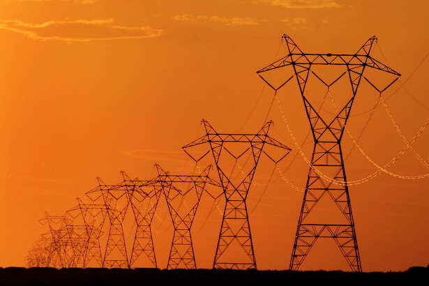 High voltage electric transmission lines are silhouetted against the late day sky near Spearville, Kan. (Associated Press File Photo)