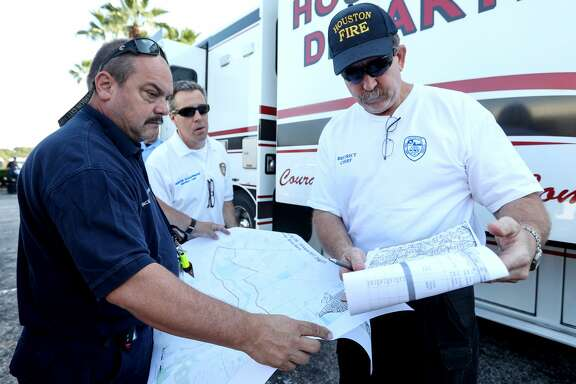 James Ingledue, with FEMA, from left, HFD District Chief Hunter Schappaugh, and District Chief Richard Cole, check maps before doing welfare checks on residents in the Meyerland area, Thursday, Aug. 31, 2017, in Houston. ( Jon Shapley  / Houston Chronicle )