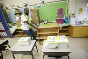 Deshawn Bonner pulls a wooden bookcase from a classrooms as crews clean at Kolter Elementary, 9710 Runnymeade Dr., Thursday, Aug. 31, 2017, in Houston. Many schools were damaged from flooding in the aftermath of Hurrican Harvey. ( Melissa Phillip / Houston Chronicle )