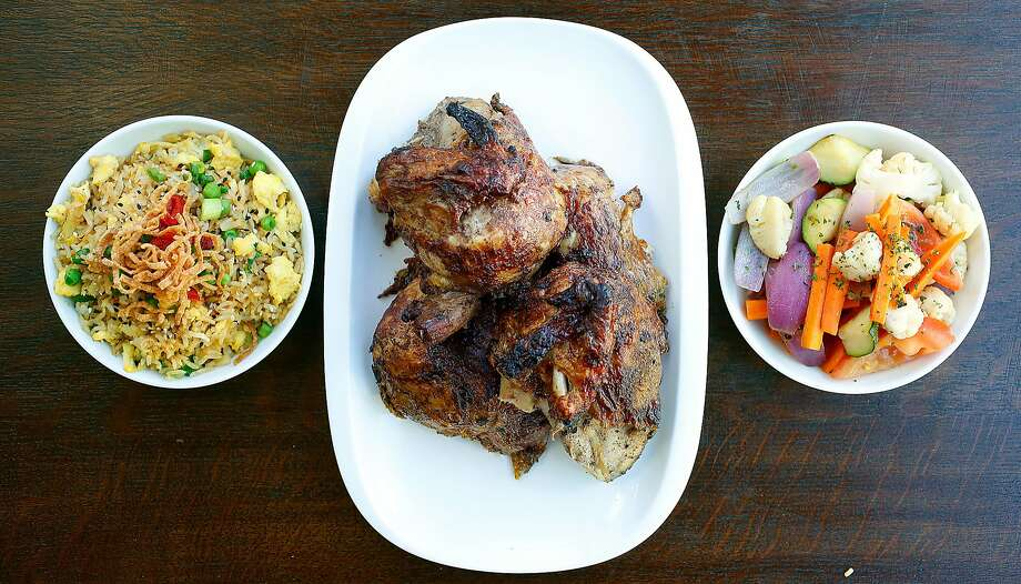 Traditional Peruvian rotisserie chicken (middle) marinated in garlic and a variety of spices overnight with Peruvian fried rice (left) and sauted vegetables (right) at Alma Cocina. Photo: Liz Hafalia, The Chronicle