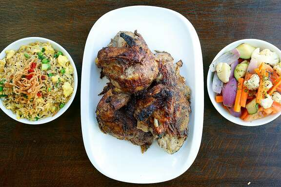 Traditional Peruvian rotisserie chicken (middle) marinated in garlic and a variety of spices overnight with Peruvian fried rice (left) and saut�ed vegetables (right) at  Alma Cocina on Thursday, September 28, 2017, in San Francisco, Calif.