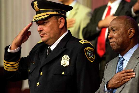 Houston Police Chief Art Acevedo, left, and Mayor Sylvester Turner stand for the National Anthem during the graduation ceremony of HPD Cadet Class 232 at Greater Grace Outreach Church on Monday, Oct. 2, 2017, in Houston. There were 59 new officers to be sworn in during the ceremony.