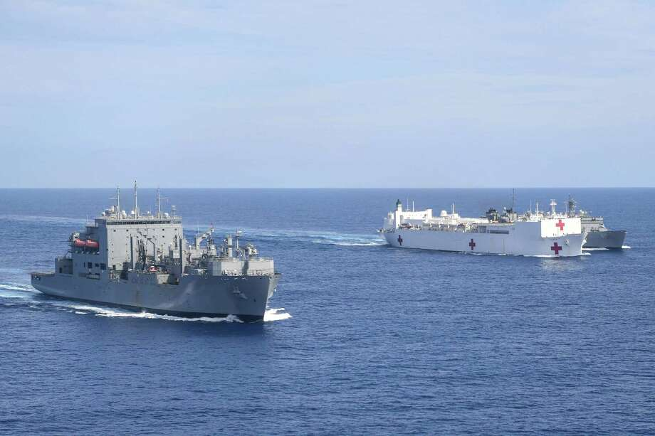 The hospital ship USS Comfort (center) underway to support relief operations in Puerto Rico, conducts a replenishment with the USS William McLean (right) with the support ship USS Supply (left) on Sunday in the Atlantic Ocean. Photo: ERNEST R. SCOTT, Handout / AFP