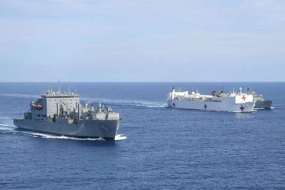 The hospital ship USS Comfort (center) underway to support relief operations in Puerto Rico, conducts a replenishment with the USS William McLean (right) with the support ship USS Supply (left) on Sunday in the Atlantic Ocean.