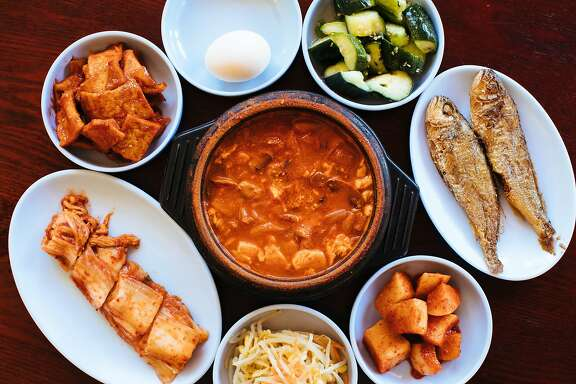 Kimchi tofu soup with banchan photographed at the My Tofu House in San Francisco, Calif. Monday, October 2, 2017.