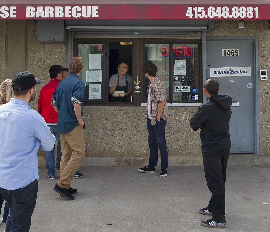 Smokin' Warehouse manager Sam Ong (center) takes orders at the Bayview barbecue spot. Photo: Liz Hafalia, The Chronicle