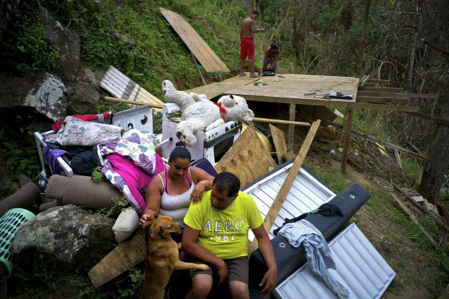 Parents look at what's left of their belongings after the hurricane, while their children build a room to protect themselves from the elements, in Morovis, Puerto Rico, on Saturday. Photo: Ramon Espinosa / Associated Press / Copyright 2017 The Associated Press. All rights reserved.