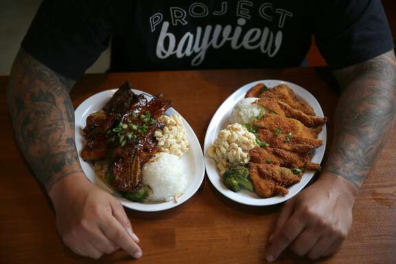 Director, pastor, and manager Shawn Gordon shows short ribs and chicken katsu plates at Huli Huli Hawaiian Grill in San Francisco, Calif., on Friday, August 21, 2015.