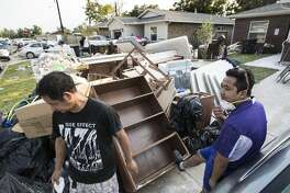 Go Tuang, left, and his brother Vial Sum takes a break outside Tuang's home damaged by floodwaters from Tropical Storm Harvey in a neighborhood built by Habitat for Humanity on Saturday, Sept. 2, 2017, in Houston. ( Brett Coomer / Houston Chronicle )