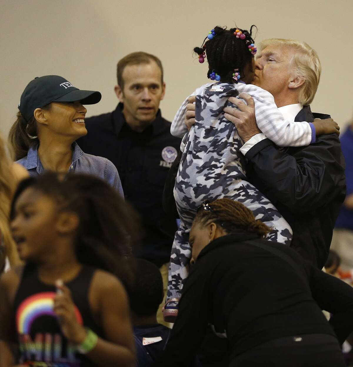 President Donald Trump kisses a child while visiting Hurricane Harvey evacuees at NRG Center in Houston. He came to Texas twice after Harvey.