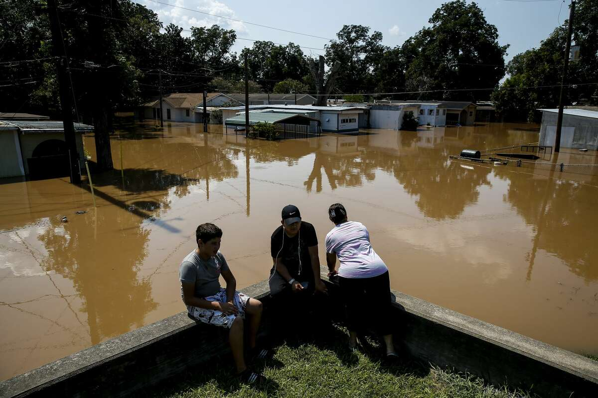 Rosalinda Gomez, right, peers down Damon Street as the flooded Brazos River runs through the neighborhood after Tropical Storm Harvey.