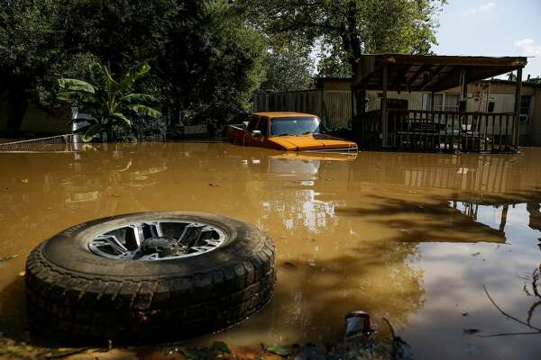 A tire floats next to a truck flooded by the Brazos River after Tropical Storm Harvey in Richmond.