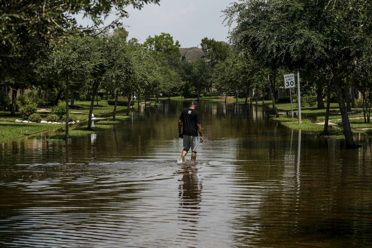 Ron Black walks down a flooded street to get to his house after Tropical Storm Harvey Friday, Sept. 1, 2017 in Sienna Plantation. Many in Houston are wading through emotional turmoil.