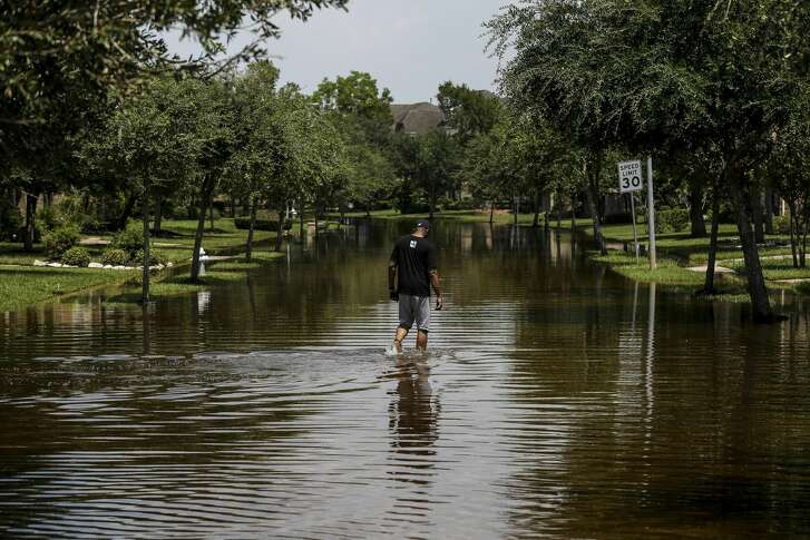 Ron Black walks down a flooded street to get to his house after Tropical Storm Harvey Friday, Sept. 1, 2017 in Sienna Plantation. ( Michael Ciaglo / Houston Chronicle)