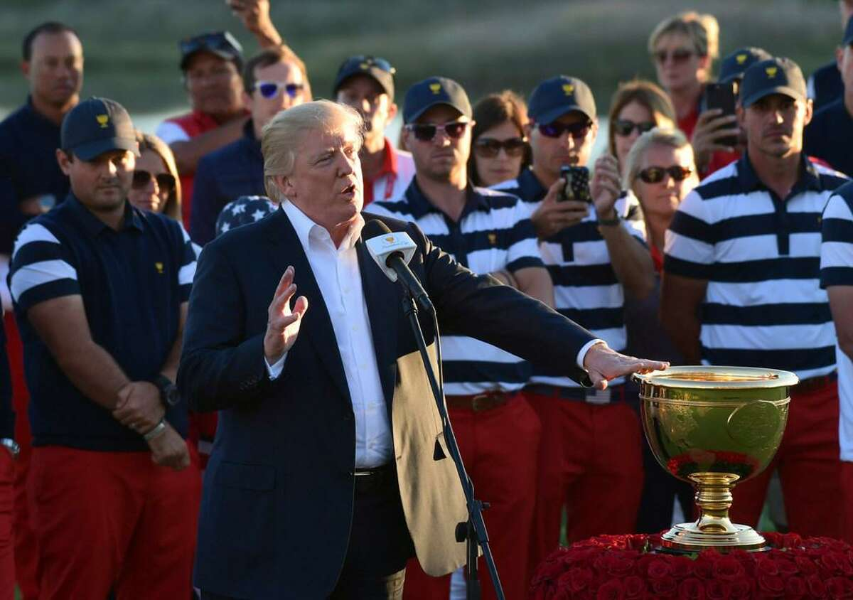 Donald Trump presents the Presidents Cup trophy to Team USA.