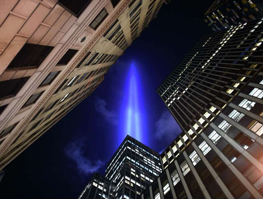 TOPSHOTS The Tribute in Light illuminates the sky  down in the Wall Street area of lower Manhattan in New York on September 10, 2014 on the night before the 13th anniversary of the September 11, 2001 attacks. The tribute, an art installation of the Municipal Art Society, consists of 88 searchlights placed next to the site of the World Trade Center creating two vertical columns of light in remembrance of the 2001 attacks. AFP PHOTO /  TIMOTHY  A. CLARYTIMOTHY A. CLARY/AFP/Getty Images Photo: TIMOTHY A. CLARY / AFP