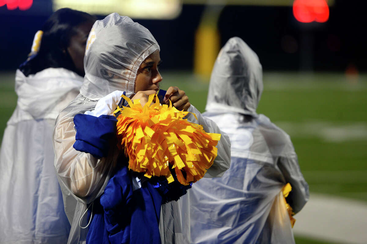 An Ozen cheerleader ties her parka before their football game against Vidor at the Thomas Center on Monday night. Photo taken Monday 10/2/17 Ryan Pelham/The Enterprise