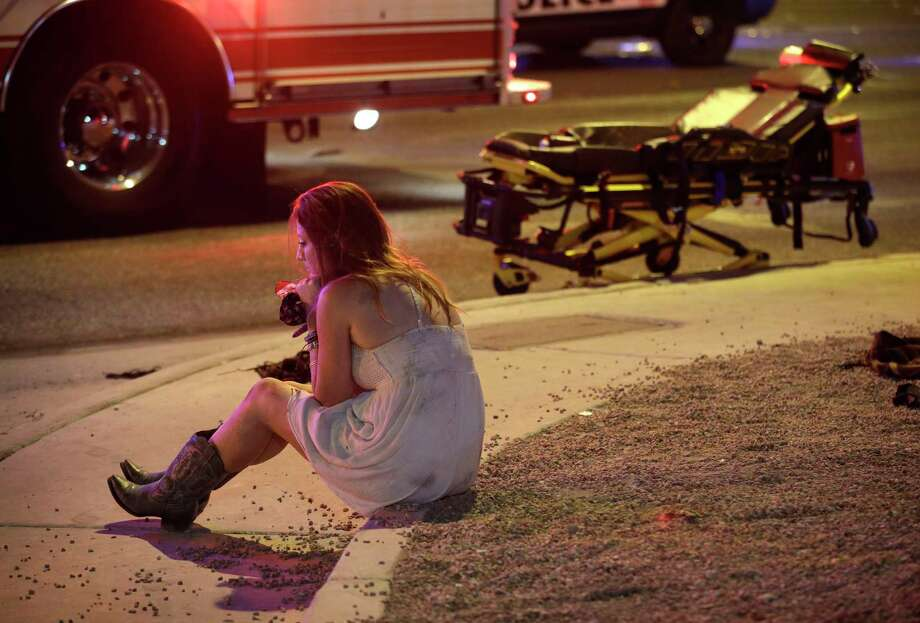 A woman sits on a curb at the scene of a shooting outside of a music festival Monday, Oct. 2, 2017, in Las Vegas. Photo: John Locher, STF / Copyright 2017 The Associated Press. All rights reserved.