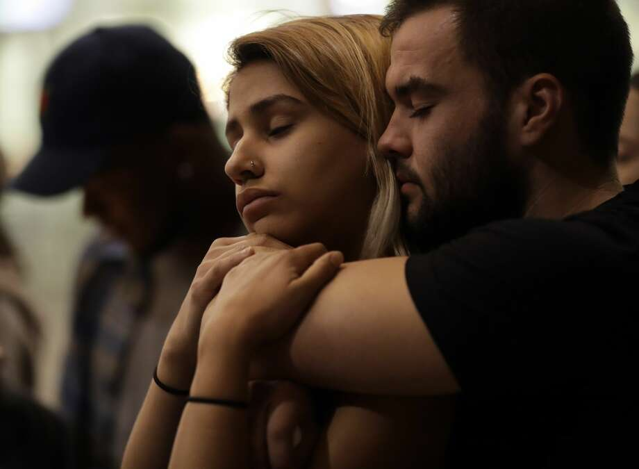 University of Nevada Las Vegas students Raymond Lloyd, right, and Karla Rodriguez take part in a vigil Monday, Oct. 2, 2017, in Las Vegas. A gunman on the 32nd floor of the Mandalay Bay casino hotel rained automatic weapons fire down on the crowd of over 22,000 at an outdoor country music festival Sunday. (AP Photo/Gregory Bull) Photo: Gregory Bull/AP