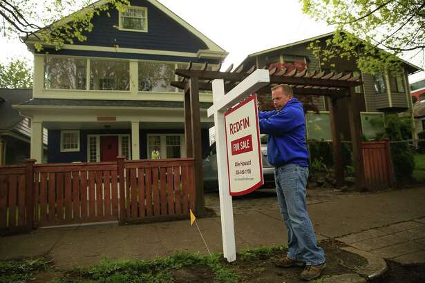 Kelly Bridgeman, with Sign Pros, installs a Redfin sign on May 6, 2015 in Madrona, Wash. Redfin has less than a 3 percent market share on its home turf. (Erika Schultz/Seattle Times/TNS)