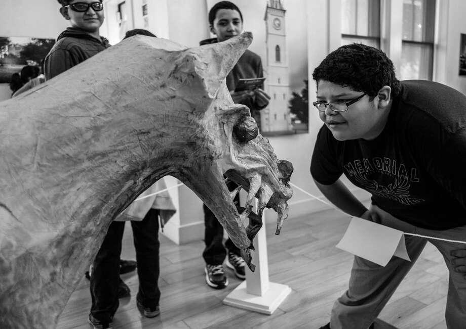"""Un joven viendo de cerca un modelo del Chupacabras de la exhibición """"Haunted Heritage"""" en el museo Villa Antigua. Photo: Foto De Cortesía"""