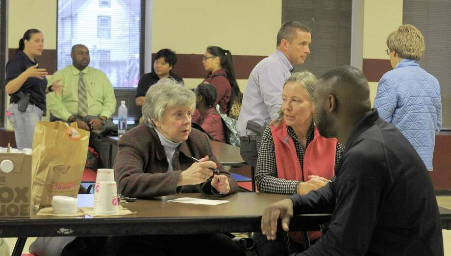 Katharine Archibald and Eileen Cottington, residents of Stamford's Waterside neighborhood, chat with Stamford Police Investigator Jerry Junes during a Coffee with a Cop event at the Trailblazer's Academy in Stamford, Conn. on March 16, 2016. Stamford police are holding the informal meet ups, as part of a community outreach program where cops are trying to have a positive dialog with the community. Photo: Matthew Brown / Hearst Connecticut Media / Stamford Advocate