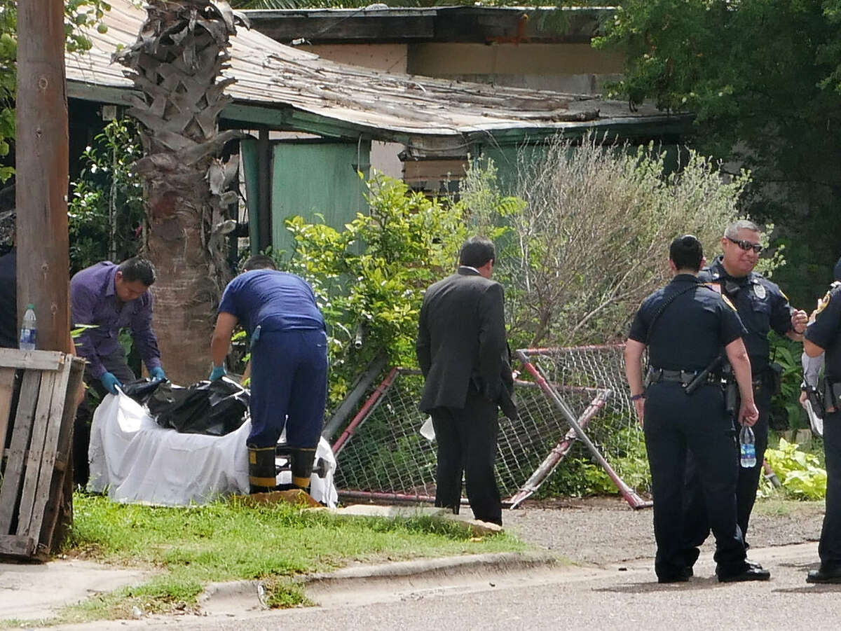 Webb County Coroner's Office personnel remove a body from the scene of a house fire in the 3400 block of San Agustin Avenue, Monday, October 2, 2017. Police are investigating the scene for the cause of the incident.