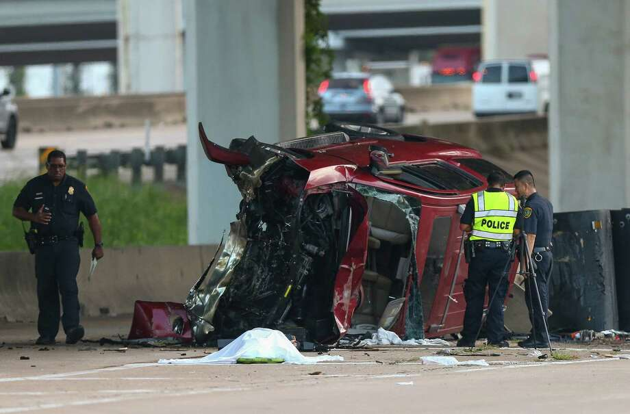 Houston Police officers investigate the scene of a fatal single-vehicle crash on the northbound lanes of the Southwest Freeway Frontage Road near Beltway 8 Tuesday, Oct. 3, 2017, in Houston. According to Sgt. Karl Harris there were two women inside the SUV, one was transported to Ben Taub  and is in critical condition. Photo: Godofredo A. Vasquez / Godofredo A. Vasquez / Houston Chronicle