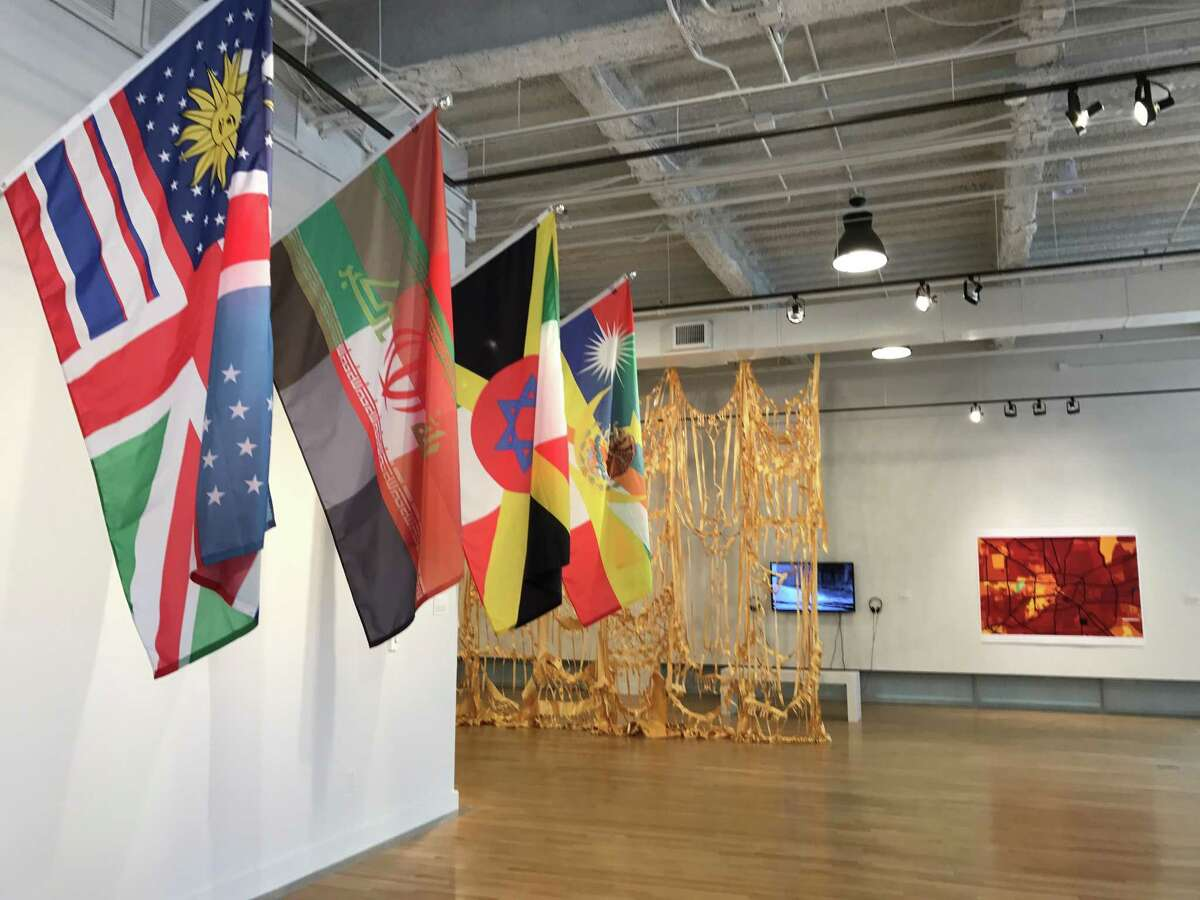 """""""Flag Fusions 20, 21, 28 and 46,"""" from Pedro Lasch's """"Abstract Nationalism"""" project, which was featured at the 2015 Venice Biennale, are in the foreground, with Margaret Griffith's hanging sculpture """"15th, 17th and Pennsylvania"""" and Phillip Pyle II's digital print """"Households"""