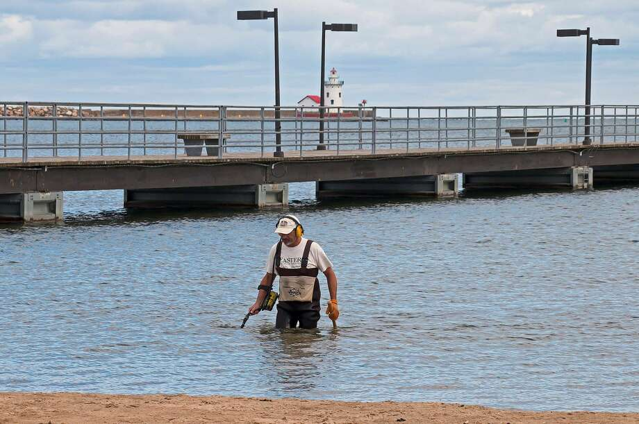 Jim Potwardowski, of Rochester, uses a metal detector to search for lost coins and rings in the waters near the Trescott Street Pier in Harbor Beach. He searches this and other Huron County beaches often and has found a number of rings and other interesting items. Photo: Bill Diller/For The Tribune