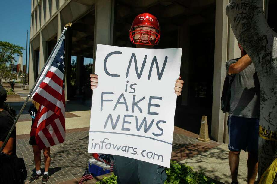 "A man holding a sign that says, ""CNN is Fake News"" and ""infowars.com"" positioned himself into photos while the media covered an Impeachment March in downtown Los Angeles on July 2, 2017. Photo: Jay L. Clendenin, TNS / Los Angeles Times"