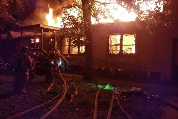 Firefighters with the East Montgomery County, Porter and Caney Creek fire departments battle an early-morning blaze that engulfed a single family home in New Caney on Tuesday, Oct. 3, 2017.